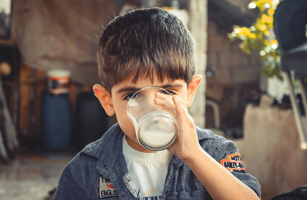 Bambino beve bicchiere di latte di qualità - guida alla scelta